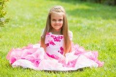 Пятилетняя девушка в красивом платье сидела на лужайке в зеленом саде Стоковое Изображение