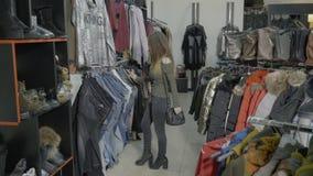 Пятки привлекательной женской модели нося просматривая одежды для того чтобы купить в моле магазина покупок - акции видеоматериалы