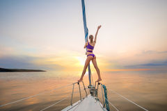 Плавание девушки на яхте на встрече солнце Стоковые Изображения
