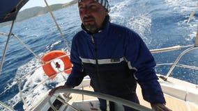Плавание молодого человека в море Шкипер яхты сток-видео