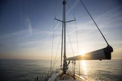 Плавание парусника в море во время захода солнца Стоковые Изображения RF