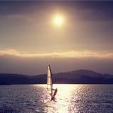 Плавание Windsurfer в ветерок сняло с нежным фильтром Сильное солнце делает отражения Стоковое Фото
