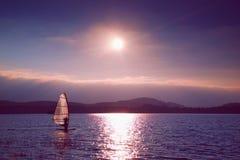Плавание Windsurfer в ветерок сняло с нежным фильтром Сильное солнце делает отражения Стоковое Изображение RF