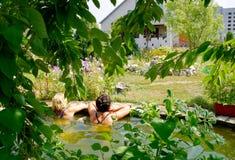 Плавать в бассейне на их коттедже лета Стоковые Изображения RF