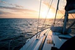 Плавать яхта на заходе солнца в открытом море стоковая фотография rf