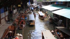 Плавая шлюпка выходит популярную туристическую достопримечательность вышед на рынок на рынок в Damnoen Saduak, Таиланде сток-видео