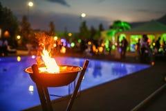 Пламенеющий факел на заходе солнца бассейном Стоковые Изображения RF