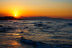 Пламенистый красный заход солнца над турбулентным морем Стоковое Изображение RF