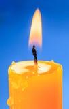 Пламя свечи над голубым backround Стоковые Изображения