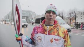 Пламя эстафетного бега олимпийское в Санкт-Петербурге в октябре Мужской torchbearer дает интервью взволнованности сток-видео