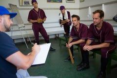 Планирование бейсбольной команды с тренером пока сидящ на стенде стоковые фотографии rf