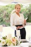 Плановик свадьбы проверяя украшения таблицы в шатёр стоковое фото rf