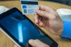 Планшет в руках людей Укомплектуйте личным составом держать ПК таблетки и кредитную карточку крытыми, ходить по магазинам онлайн стоковая фотография rf