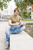 Планшет компьтер-книжки человека в улице стоковые фото