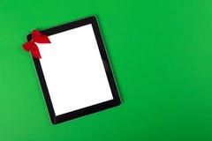 Планшет с смычком на зеленой предпосылке Стоковая Фотография RF