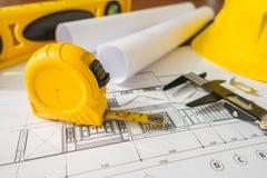 Планы строительства с желтым шлемом и чертегные инструменты на bluep Стоковые Фото