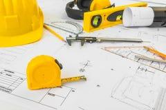 Планы строительства с желтым шлемом и чертегные инструменты на bluep Стоковые Изображения RF