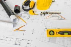 Планы строительства с желтым шлемом и чертегные инструменты на bluep Стоковое фото RF