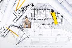 Планы строительства с чертегными инструментами и миниатюрой дома на голубом Стоковые Фотографии RF