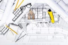 Планы строительства с чертегными инструментами и миниатюрой дома на голубом Стоковые Изображения
