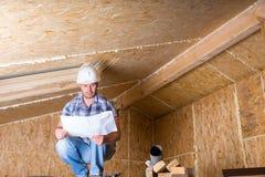Планы чтения построителя внутри незаконченного дома Стоковая Фотография