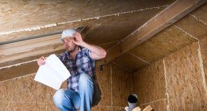 Планы чтения построителя внутри незаконченного дома Стоковые Фотографии RF