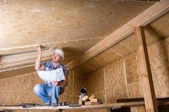 Планы чтения построителя внутри незаконченного дома Стоковые Фото