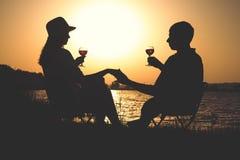 План молодых пар ослабляя на банке реки на зоре с бокалом вина на стульях стоковые изображения rf