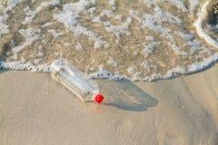 Пластичная бутылка питья на пляже, концепции воды на пляже Стоковое фото RF