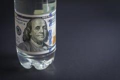 Пластичная бутылка с деноминацией 100 долларов вместо ярлыка Стоковое фото RF