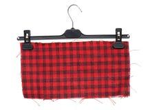 Пластичная вешалка одежд с смертной казнью через повешение на ей часть checkered Стоковые Фотографии RF