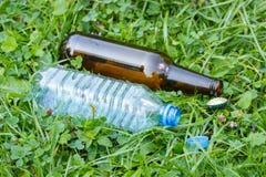Пластичная и стеклянная бутылка с крышками бутылки на траве в парке, засаривать окружающей среды Стоковые Фото