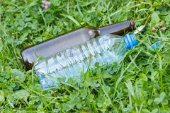 Пластичная и стеклянная бутылка с крышками бутылки на траве в парке, засаривать окружающей среды Стоковые Фотографии RF