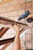 Пластичная установка окна Работник прикрепляет анкерную доску с отверткой стоковая фотография rf