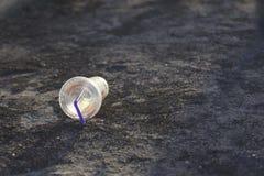 Пластичная чашка на земле Стоковая Фотография RF