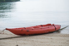 Пластичная шлюпка припаркованная на пляже песка и имеет море предпосылка T Стоковое Изображение RF