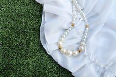 Пластичное ожерелье perl на белой ткани стоковые изображения