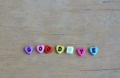 Пластичное письмо аранжирует до свидания слово на деревянной доске стоковое фото