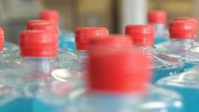 Пластичные бутылки заполнили с голубой жидкостью, движением вдоль конвейерной ленты 4K видеоматериал