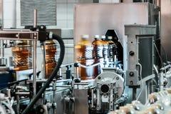 Пластичные бутылки заполнили с пивом на транспортере машины завалки Стоковые Изображения
