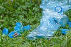 Пластичные бутылки и крышки бутылки на зеленой траве в парке, концепции засаривать окружающей среды Стоковая Фотография RF