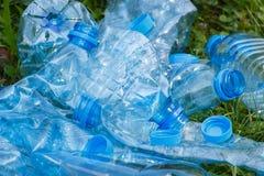 Пластичные бутылки и крышки бутылки на зеленой траве в парке, концепции засаривать окружающей среды Стоковые Фотографии RF