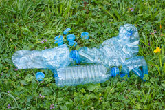 Пластичные бутылки и крышки бутылки на траве в парке, засаривать окружающей среды Стоковые Изображения