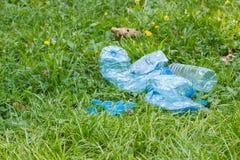 Пластичные бутылки и крышки бутылки на траве в парке, засаривать окружающей среды Стоковые Изображения RF