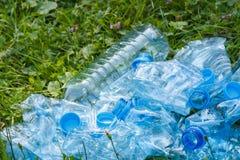 Пластичные бутылки и крышки бутылки на траве в парке, засаривать окружающей среды Стоковая Фотография
