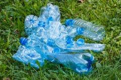 Пластичные бутылки и крышки бутылки на траве в парке, засаривать окружающей среды Стоковое фото RF