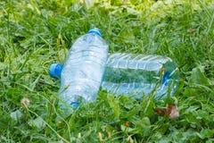 Пластичные бутылки минеральной воды на траве в парке, засаривать окружающей среды Стоковое Изображение RF