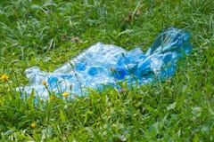 Пластичные бутылки минеральной воды на траве в парке, засаривать окружающей среды Стоковое Фото