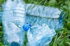 Пластичные бутылки минеральной воды на траве в парке, засаривать окружающей среды Стоковые Изображения