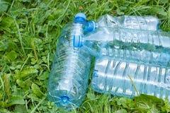 Пластичные бутылки минеральной воды на траве в парке, засаривать окружающей среды Стоковое Изображение